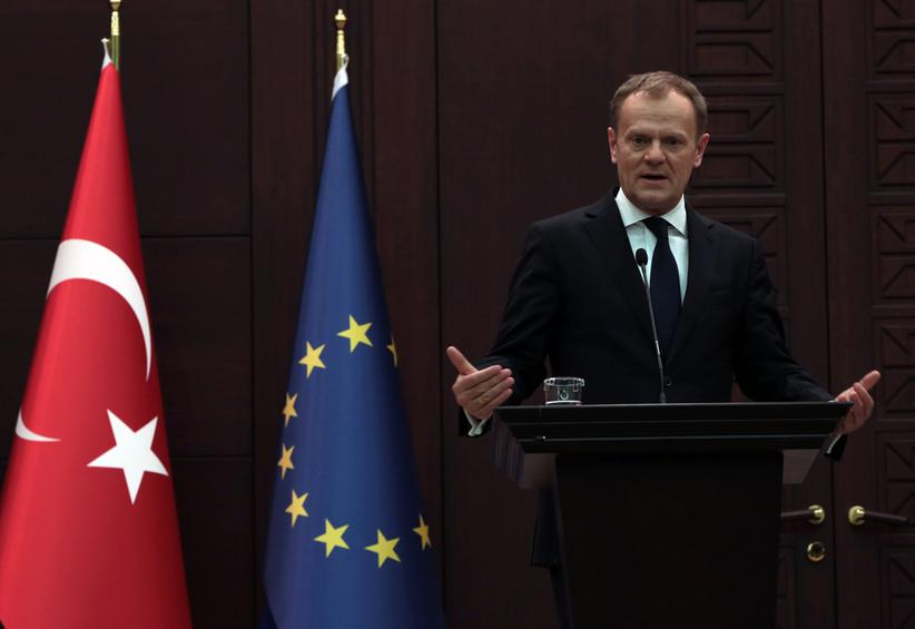 "European Council President Donald Tusk speaks to the media during a joint press conference with Turkish Prime Minister Ahmet Davutoglu in Ankara, Turkey, Thursday, March 3, 2016. Tusk says it is up to Turkey to decide what further measures it can take to reduce the flow of migrants but says many in Europe favor a mechanism that would allow the ""fast and large-scale"" shipment of migrants back to Turkey and such a mechanism would ""effectively break the business model of the smugglers.(AP Photo/Burhan Ozbilici)"